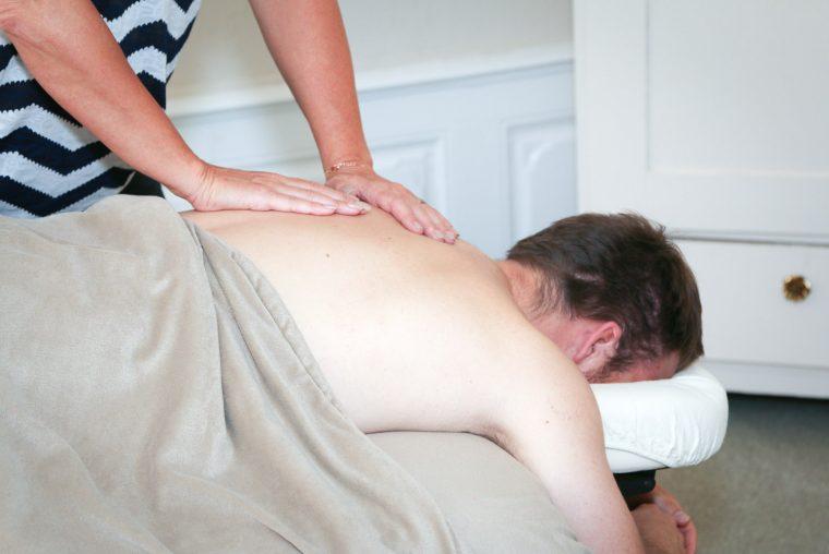 Fysiurgisk og body relief massage behandling af kunde som ligger på en briks