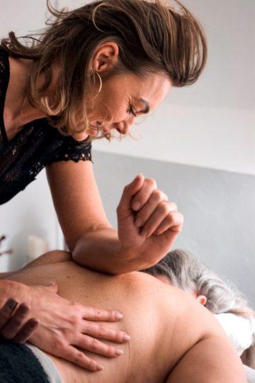 Malue Sommer giver fysiurgisk massage af en kunde med sin underarm.