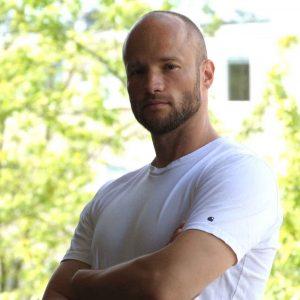 Mand står på et balkon i solskin. Profil billede til en testimonial.