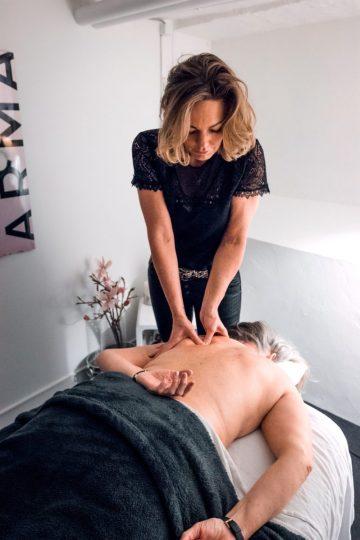 Malue Sommer giver fysiurgisk massage af en kunde på briksen med udstrakte arme.